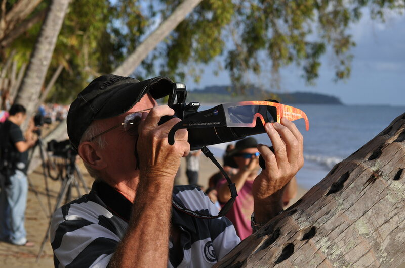 An eclipse chaser holds his special viewing glasses up to a camera during the Australian eclipse.