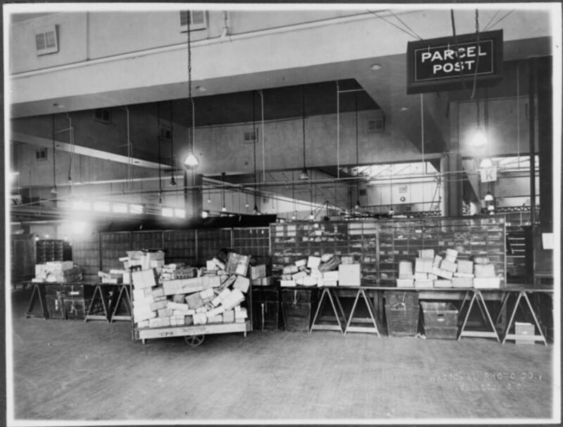 Parcel post area of mail room showing trucks and tables stacked with packages, U.S. Post Office, Washington, D.C, c. 1920