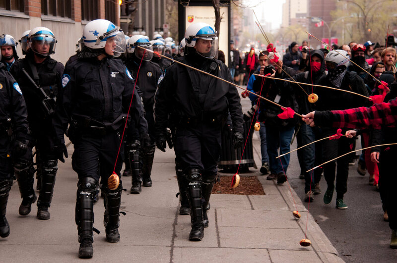 Protesters dangling donuts in front of riot cops in Montreal. (Photo: Alexis Gravel/Flickr)