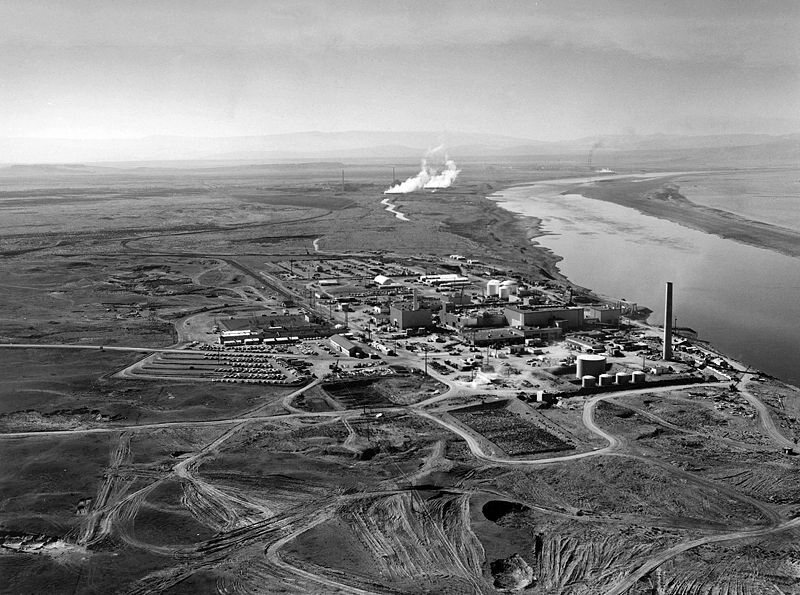 Nuclear reactors line the riverbank at the Hanford Site along the Columbia River in January 1960. The N Reactor is in the foreground, with the twin KE and KW Reactors in the immediate background. The historic B Reactor, the world's first plutonium production reactor, is visible in the distance.