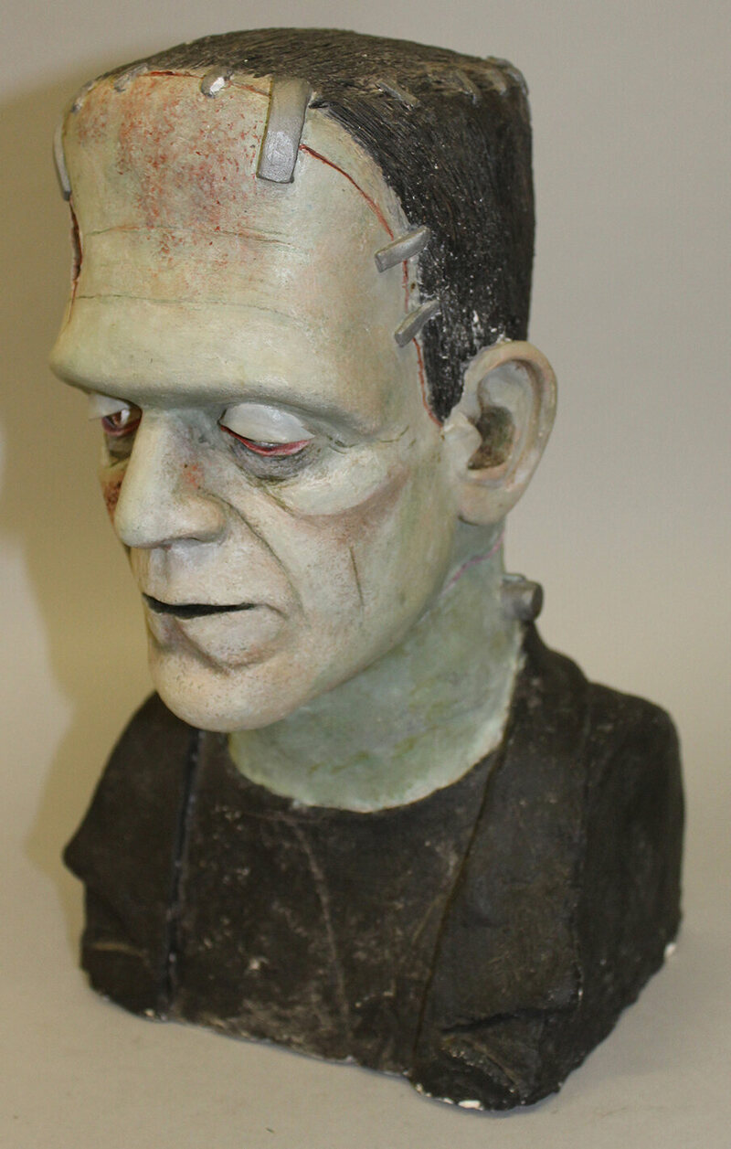 "A painted plaster bust of Frankenstein Monster, signed on white label on reverse, 11"" high       £50 – 100"