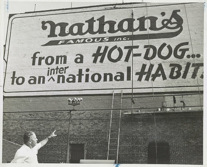 Photograph showing Nathan Handwerker pointing to restaurant sign painted on outside wall.