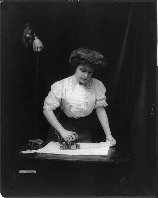 A woman uses an electric iron plugged into light socket, c. 1908.