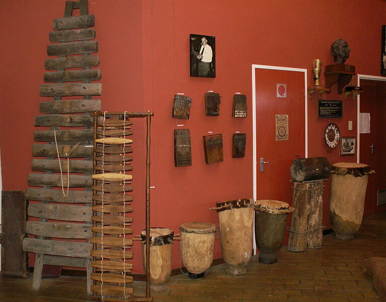 Inside ILAM, The akadinda (large xylophone), kalimbas on the wall, and a photo of Hugh Tracey.