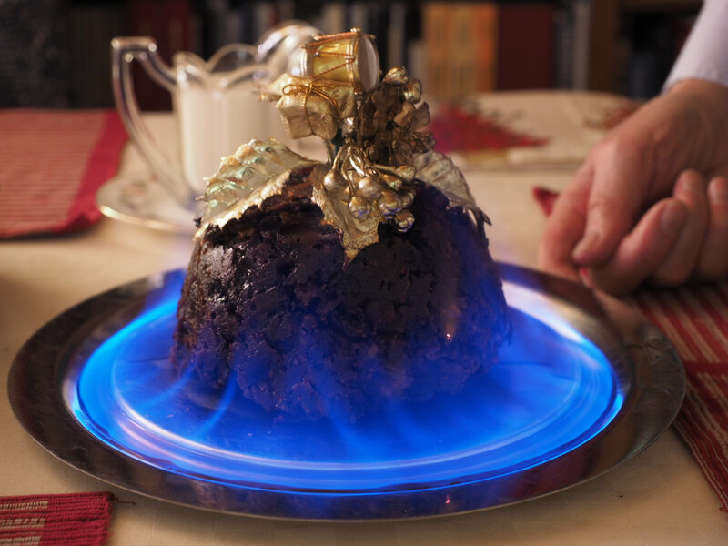 A traditional British Christmas Pudding, decorated with holly and set alight before eating.