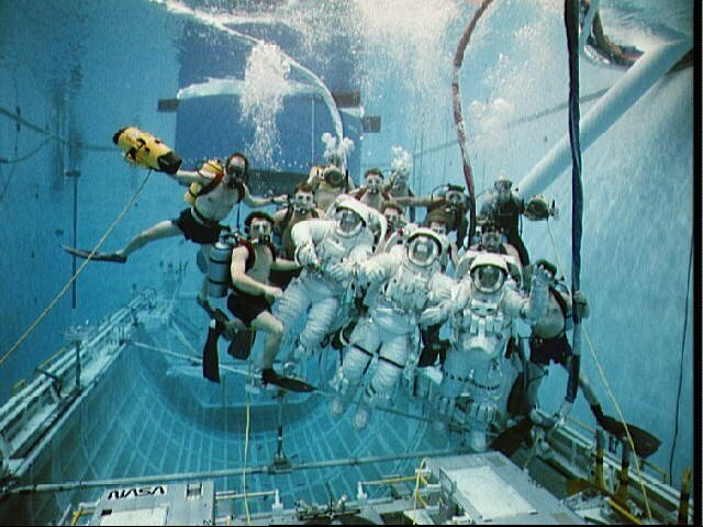 1992: In this underwater group portrait, eleven SCUBA-equipped divers pose with the three trouble shooting astronauts. Astronauts are (left to right) Clifford, Musgrave, and Voss.