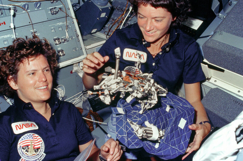 "(October 6, 1984) Astronauts Kathryn D. Sullivan, left, and Sally K. Ride display a ""bag of worms."" The ""bag"" is a sleep restraint and the majority of the ""worms"" are springs and clips used with the sleep restraint in its normal application. Clamps, a bungee cord and velcro strips are other recognizable items in the ""bag."