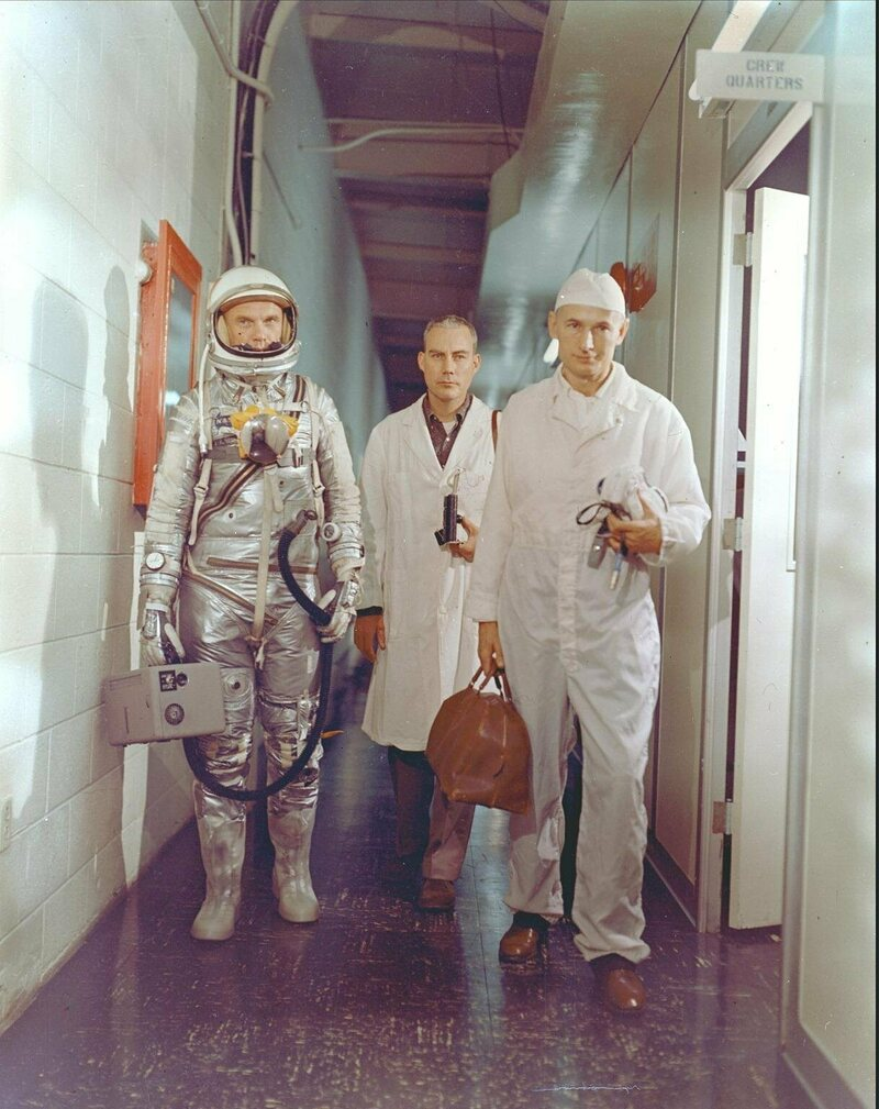 Astronaut John H. Glenn Jr., NASA flight surgeon William Douglas and equipment specialist Joseph W. Schmidt leave crew quarters prior to the Mercury-Atlas 6 mission. Glenn is in his pressure suit and is carrying the portable ventilation unit.