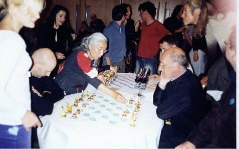 Saito takes on a fellow Fluxus partygoer in a game of Canapé Chess.