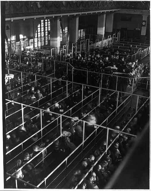 "Emigrants in ""pens"" at Ellis Island, New York, probably on or near Christmas --note the decorations]"