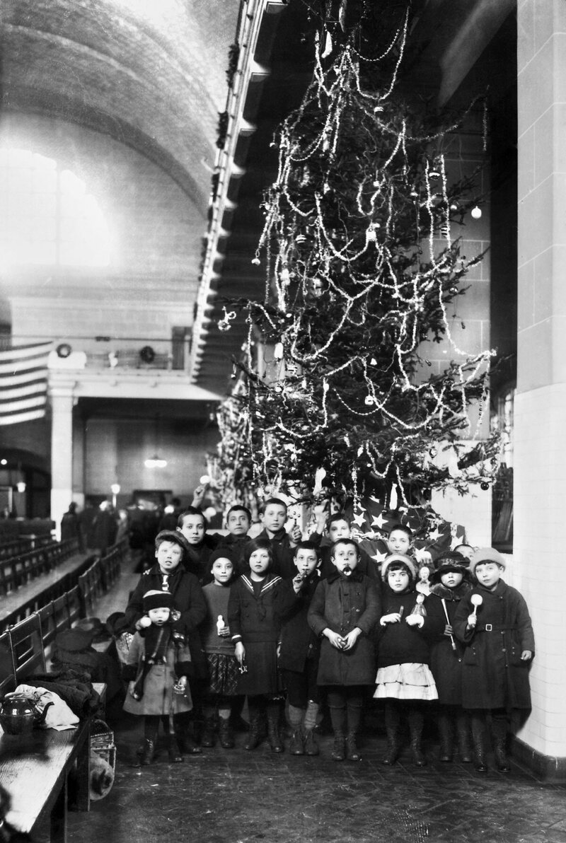 ELLIS ISLAND: CHRISTMAS, 1920. Group of immigrant children photographed in front of a Christmas tree inside the registry room at Ellis Island, New York City, 1920.
