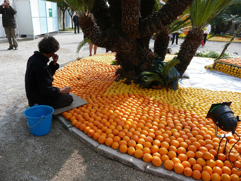 A sculptor replaces a piece of pilfered fruit at the 2013 festival.