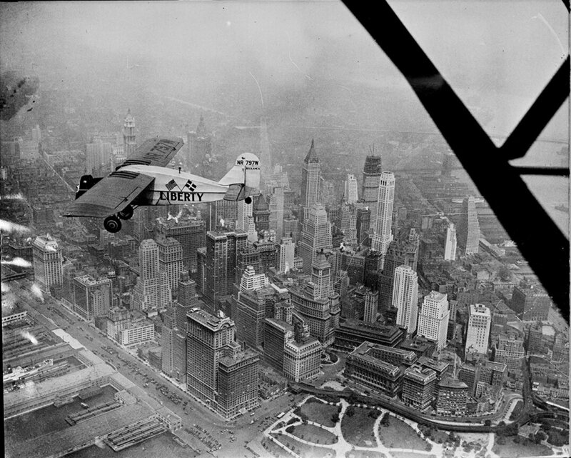 """Liberty bellanca monoplane in the air (over N.Y.C.) on first leg of its flight to Denmark. From Hasbrouck Heights, N.J. with Otto Hillig of Liberty, N.Y., flying photographer and Capt. Hoérüs, the pilot"""