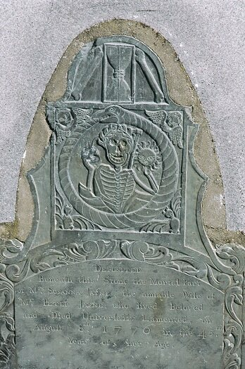 The flamboyant Tombstone of Susanna Jayne in the Old Burial Hill in Marblehead, Massachusetts, and its hourglass flanked with human bones.
