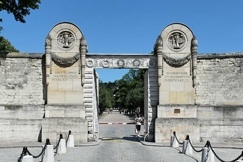 The colossal portal of Père Lachaise Cemetery in Paris and its winged hourglasses.