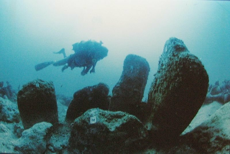 A diver passes by rock formations