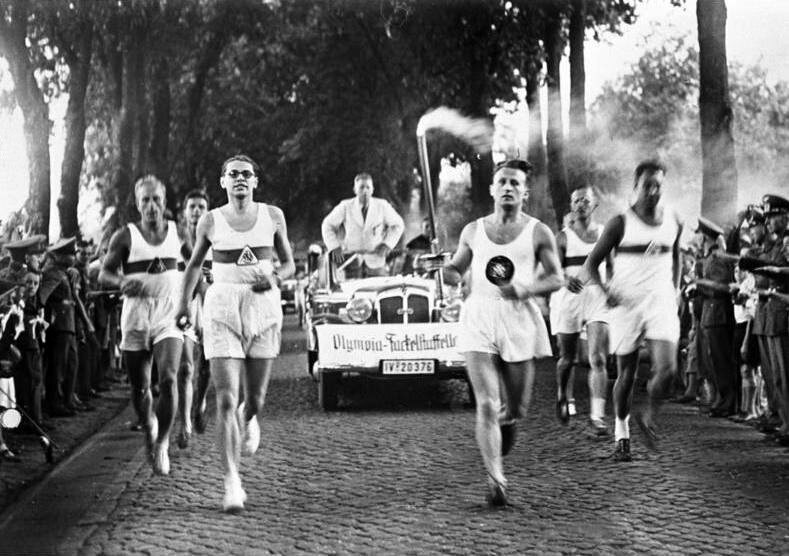 Runners carry the Olympic Flame from Greece to Germany in 1936.
