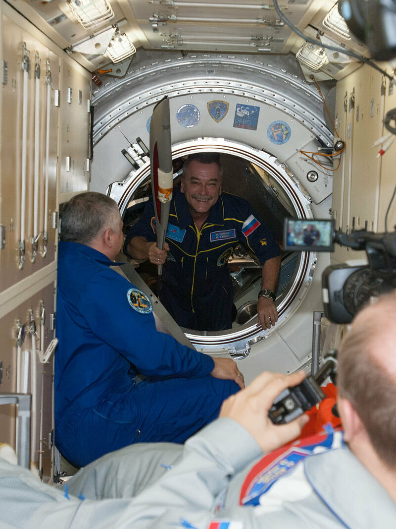 Cosmonaut Mikhail Tyurin carries the torch into the ISS in 2013.