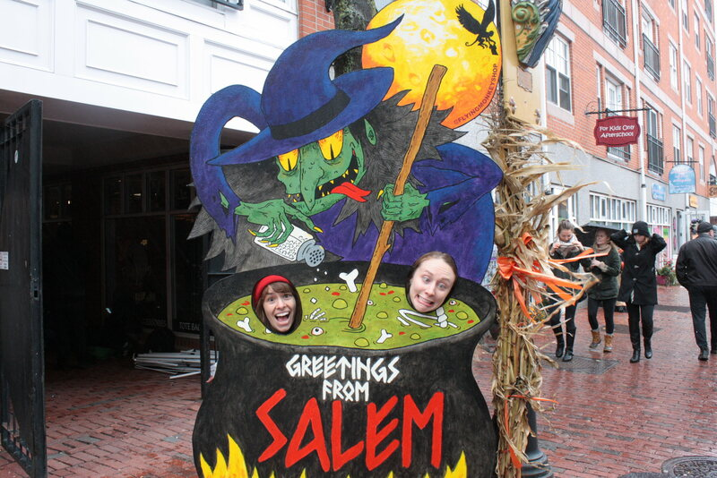 Tourists enjoy some witch-themed plywood cutouts.