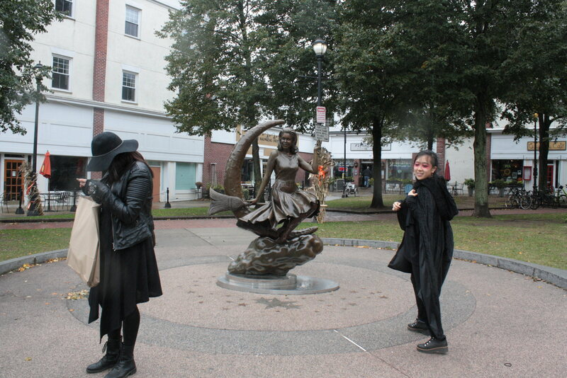A couple of dressed-up tourists pay homage to Salem's Bewitched statue.