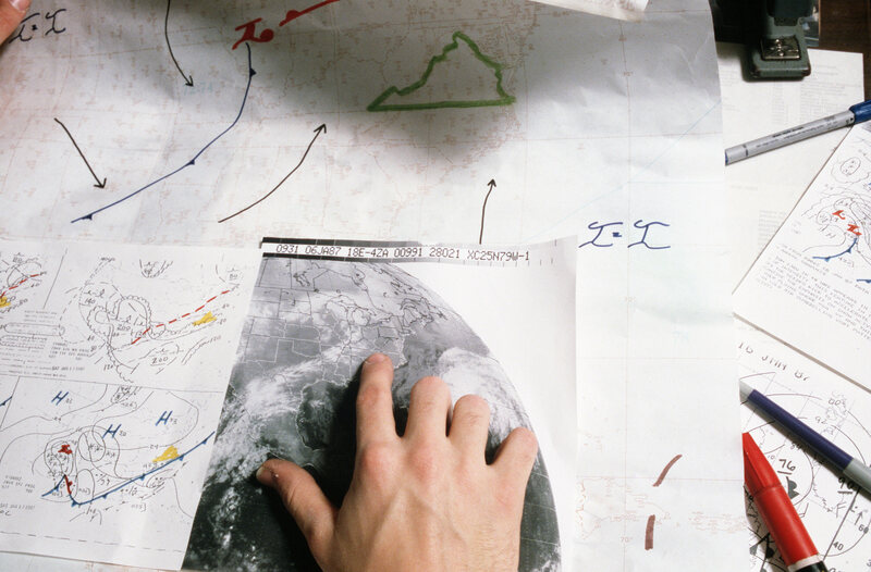 An An aerographer aboard an aircraft carrier plots the progress of a storm front on a weather map, 1985.