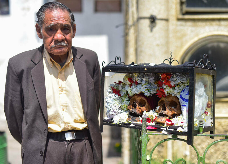 An elderly La Paz businessman poses with a pair of natitas he has owned for several decades.