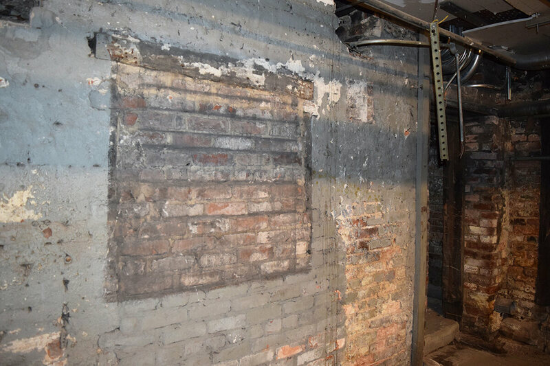 Another filled window in the Loveman Building basement with a door leading to an adjoining room.