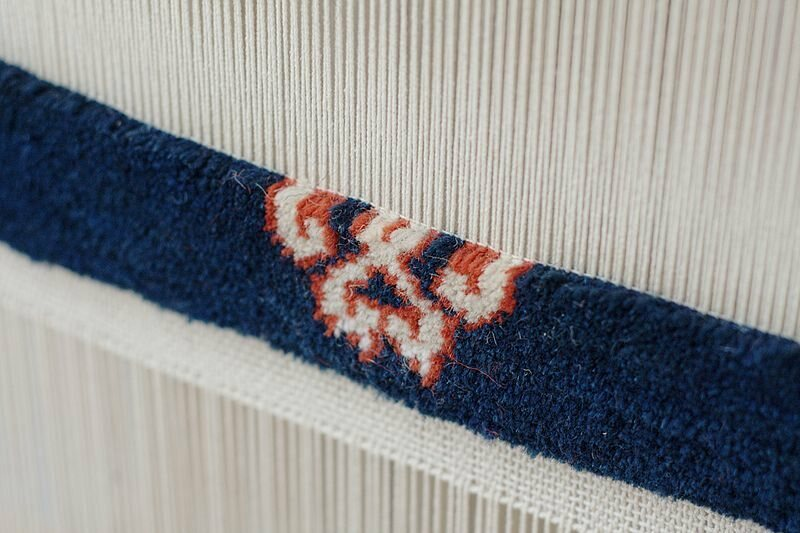 A carpet loom in action.