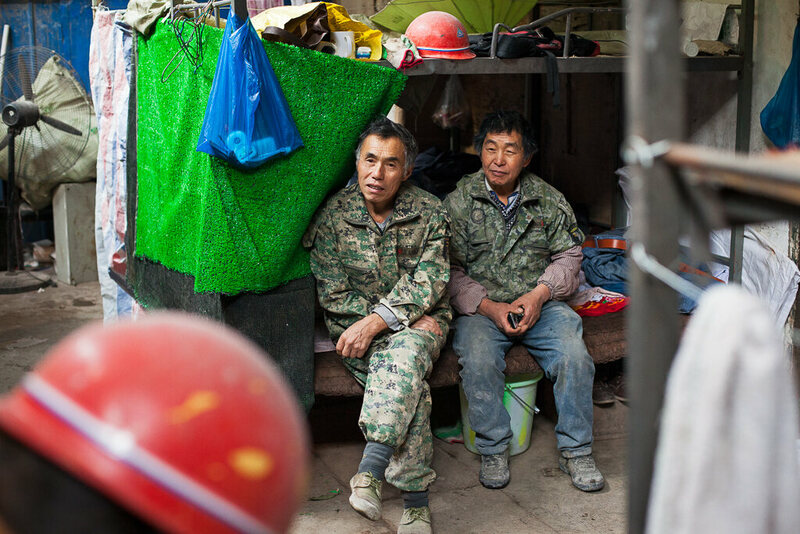 "Space is tight and these men share the bottom bunk, leaving the top for their possessions. There is a close bond between the workers, they regard each other ""like family"", as one employee puts it."