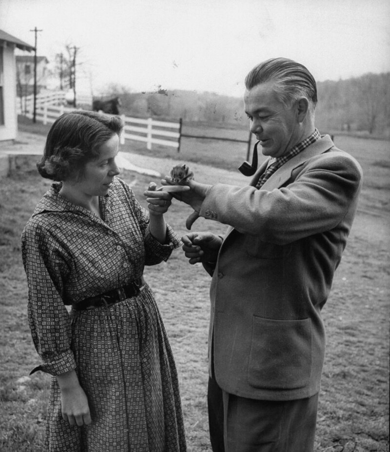 Keller Breland holding a small hamster on his hand while his wife, Marian.