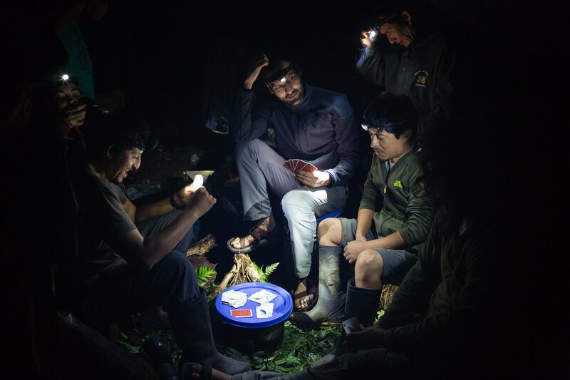 The team members play cards by the light of their headlamps.