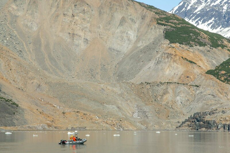 The giant scar of the landslide is put into perspective by the skiff surveying the damage.