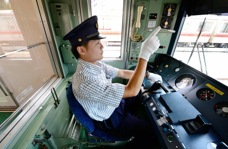 A Tokyo train driver pointing at meters on the dashboard.