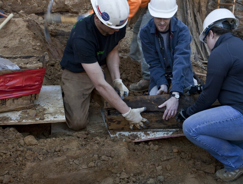 Contractors help unearth a coffin at the 218 Arch Street construction site in Philadelphia.
