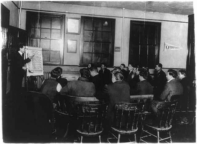 Italian class receiving instruction in English and citizenship, at the Y.M.C.A in Newark, New Jersey, c. 1920.