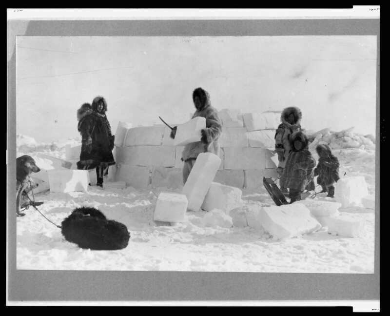 An Inuit family poses for a photo while building an igloo in 1924.