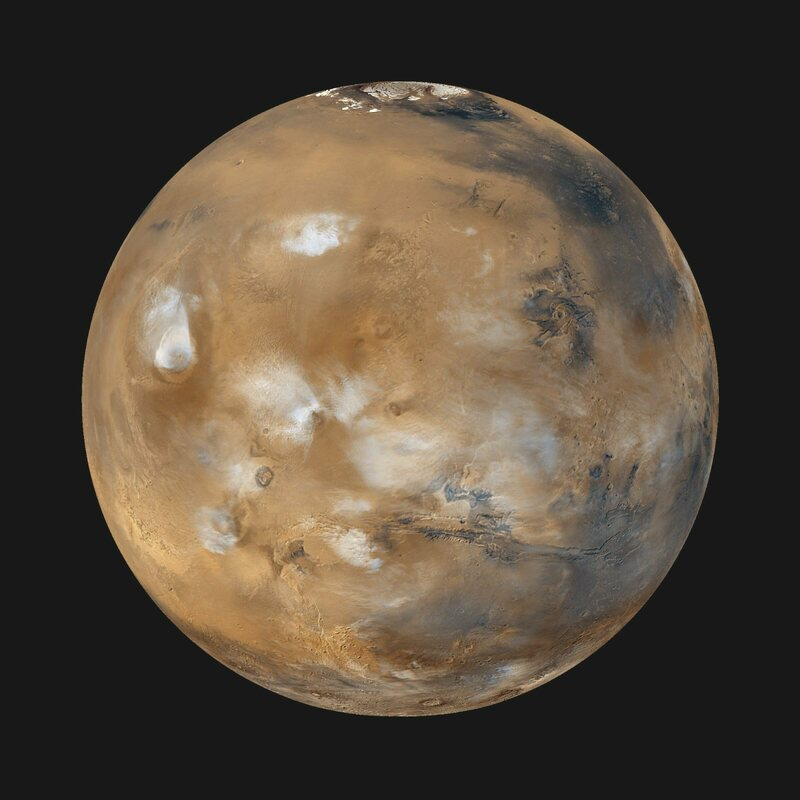A view of Mars, showing ice clouds hanging above the Tharsis volcanoes.