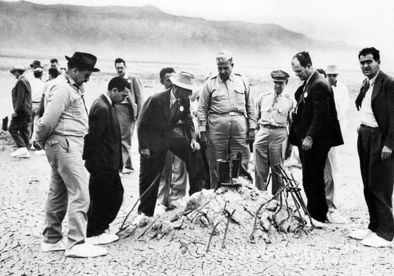 J. Robert Oppenheimer (in the hat) stands on the remains of the test site tower during a September 1945 press conference.