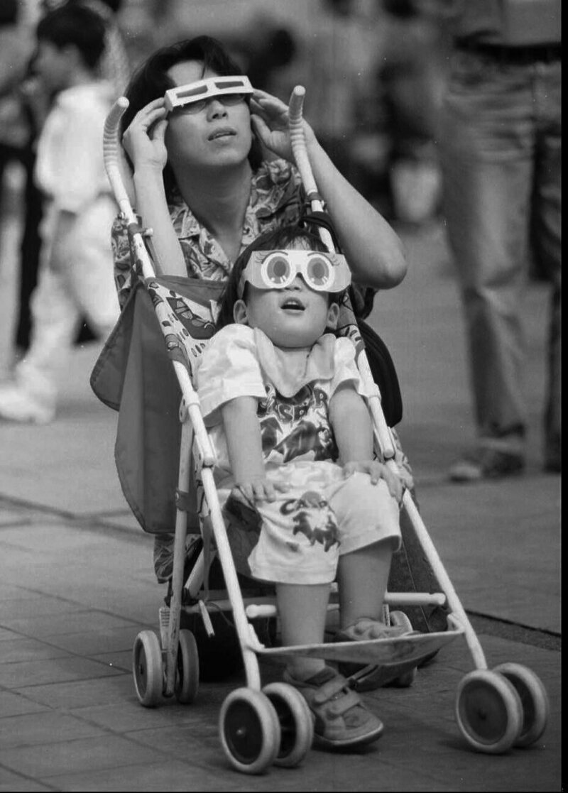 A mother and her son watch the solar eclipse in Bangkok, Thailand, 1995.