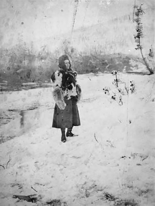 Fannie Quigley in Alaska, standing in the snow wearing a skirt and a fur parka.