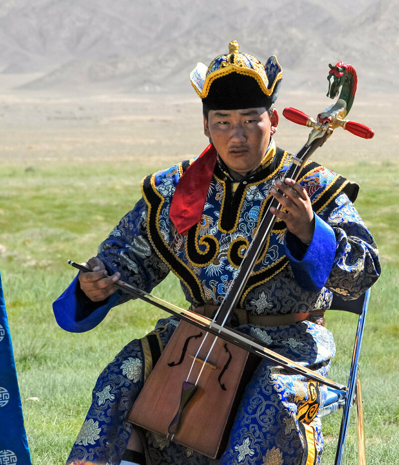 A young Mongolian nomad plays the <em>morin khuur</em>, or horsehead fiddle.