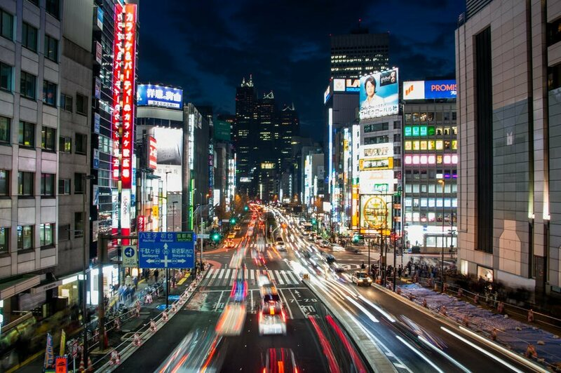 A busy Tokyo street with a line of green lights.