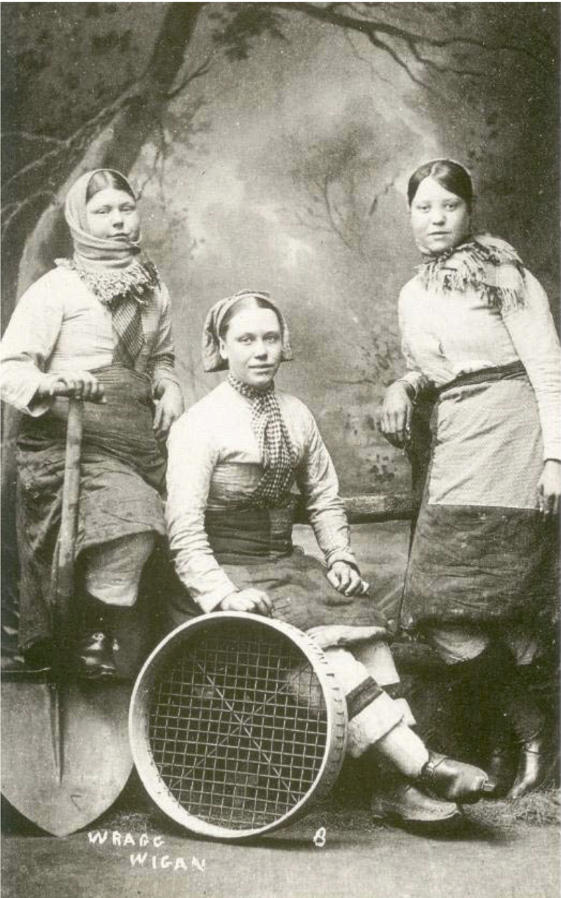 "Three Wigan ""pit lasses"" in their customary costume of trousers, skirt and clogs."