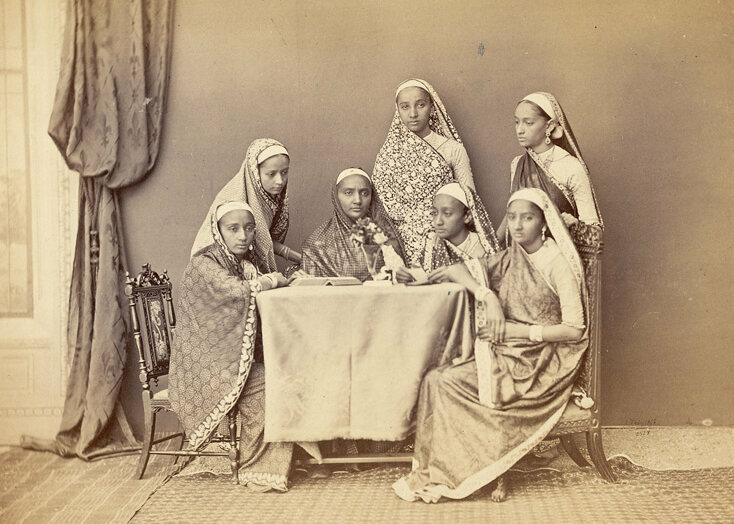 Parsi women around a table, c. 1860s.