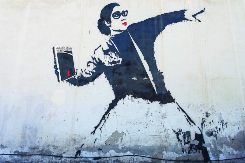 "An adaptation of Banksy's ""Flower Bomber,"" this depicts a librarian in protest, throwing Margaret Atwood's <em>A Handmaid's Tale</em>."