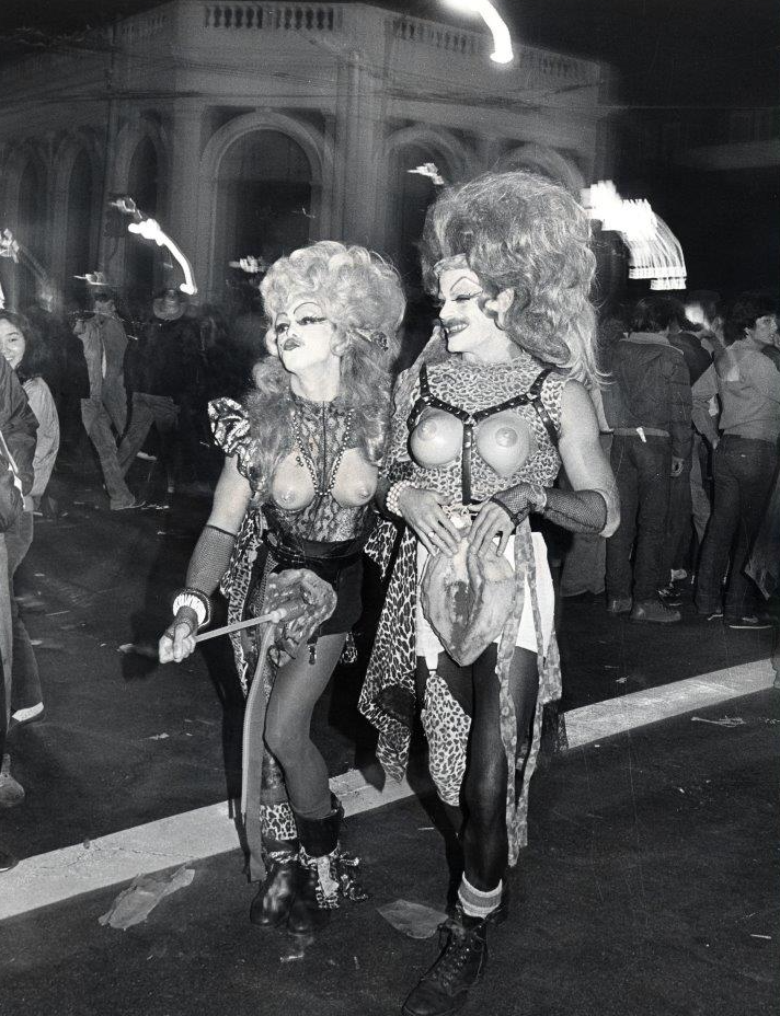 Two men dressed in drag costumes posing on Castro Street, Halloween 1982.