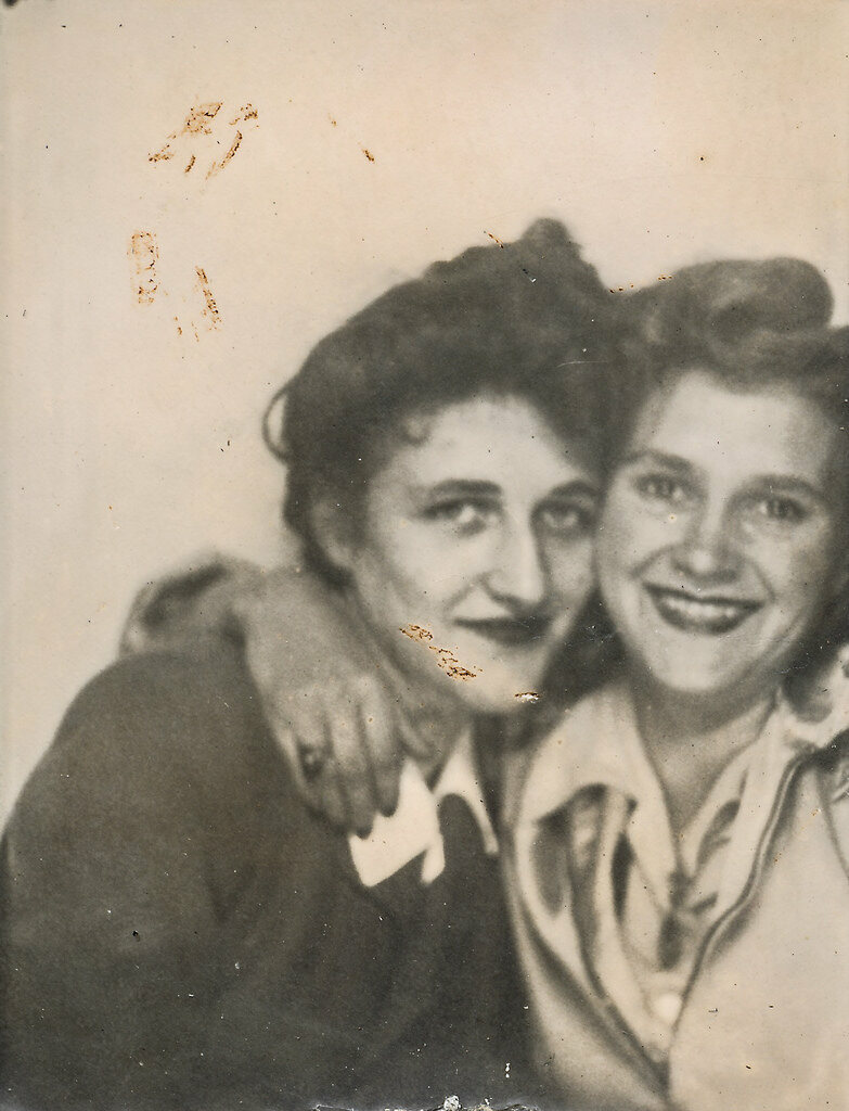 Two friends pose for a picture in a photo booth, date unknown.