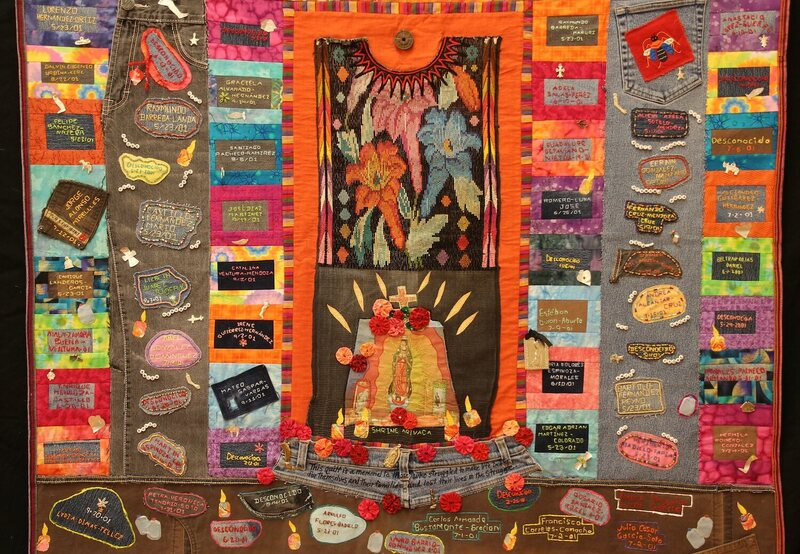 A quilt from the Migrant Quilt Project. The quilts list names of migrants who died in the Arizona desert and incorporate personal items found along migrant routes, such as jeans and handkerchiefs.
