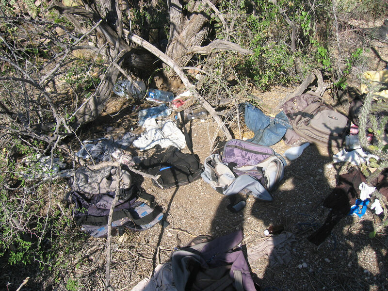 A site in the Arizona desert is seen, covered by clothing and other trash believed to be left behind by migrants.