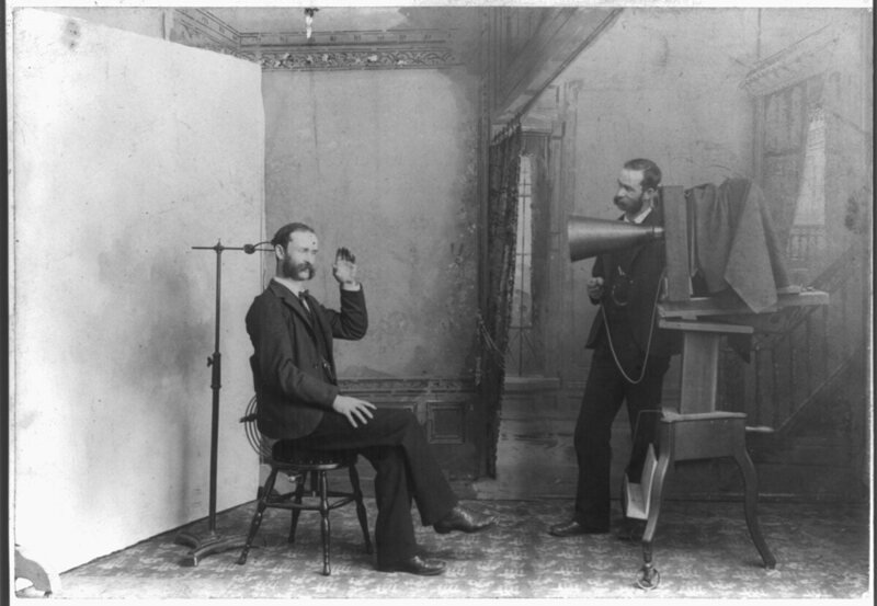 A photographer appears to photograph himself, with a large view camera and an adjustable head clamp apparatus.
